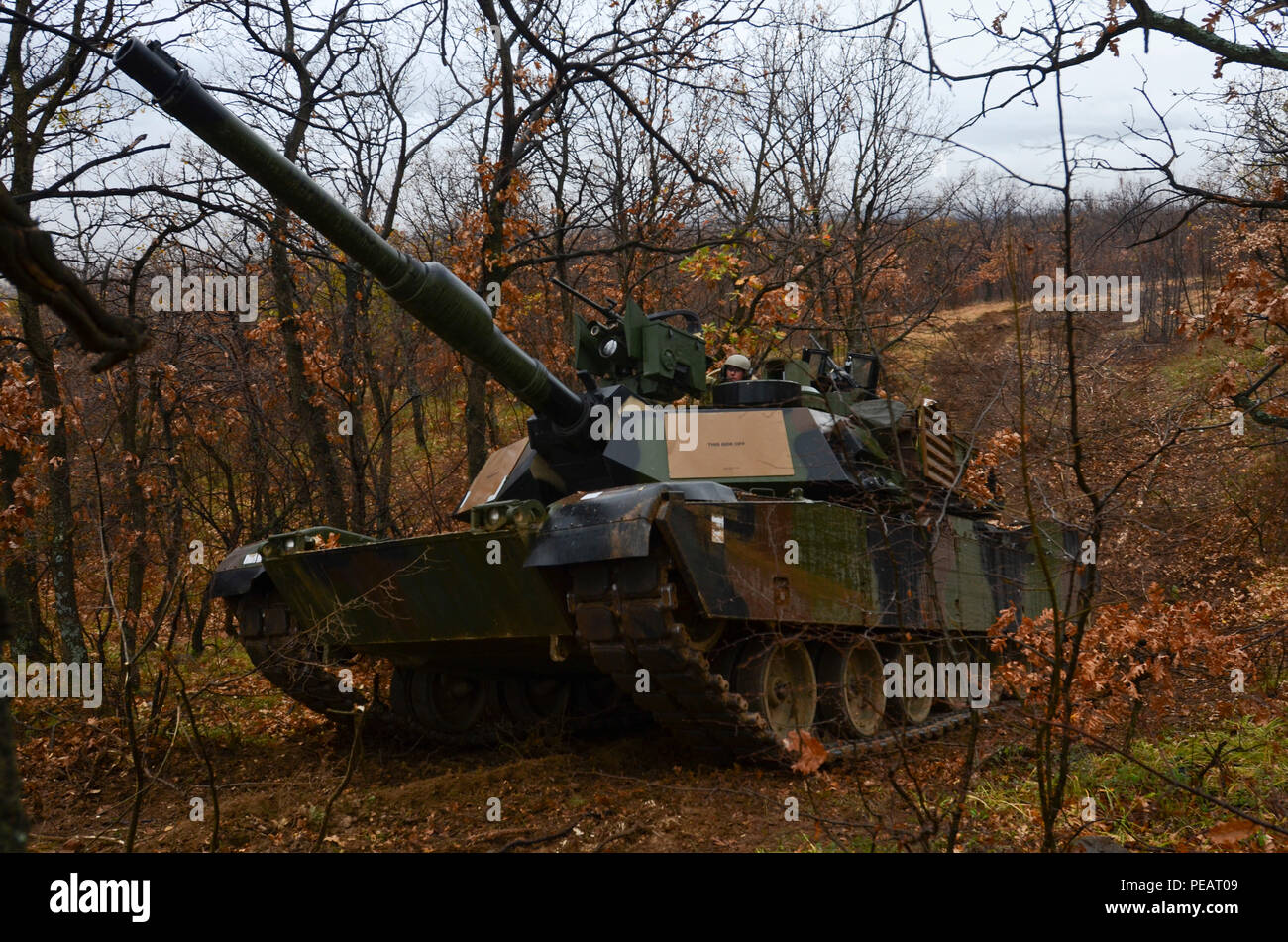 Soldiers of 5th Squadron, 7th Cavalry Regiment, 3rd Infantry Division, stationed at Fort Stewart, Ga., drive an M1A2 System Enhancement Package Version 2 Abrams tank through the mountainside during Exercise Peace Sentinel at Novo Selo Training Center, Bulgaria, Nov. 23, 2015. (Photo by Staff Sgt. Steven M. Colvin/Released) - Stock Image
