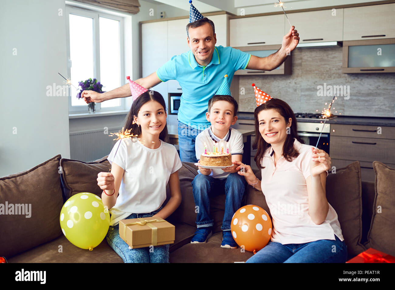 Happy family with cake on birthday party - Stock Image
