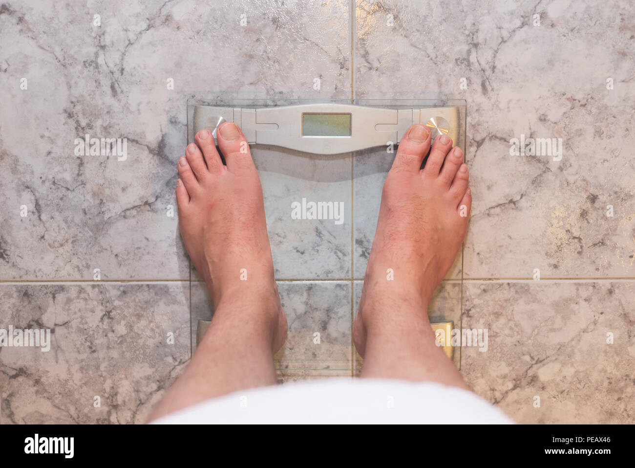 Man feet standing on weight scale - Stock Image