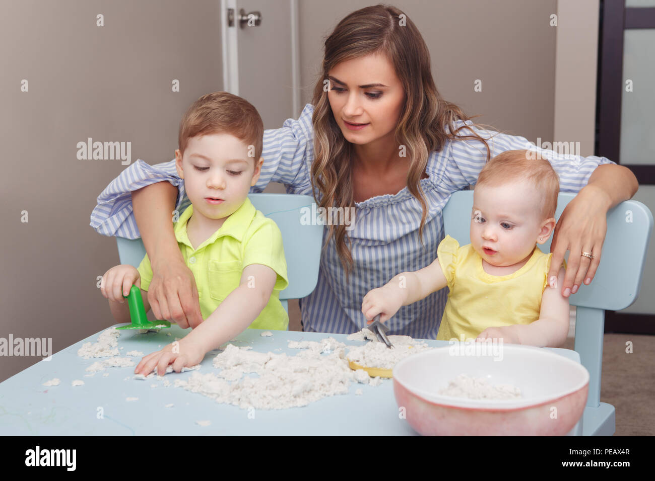 Group portrait of young white Caucasian mother with children playing kinetic sand together at home. Early creativity brain development concept. Lifest - Stock Image