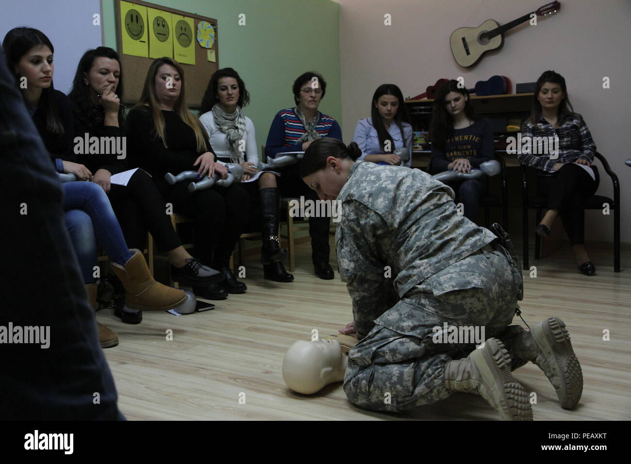 U.S. Army Staff Sgt. Sara Motyka, a Connecticut National Guard Soldier deployed to Kosovo with 1st Battalion, 169th Aviation Regiment, demonstrates the proper technique for chest compressions during a Nov. 14, 2015, CPR certification class for teachers and caregivers at the PEMA Daycare Center in Pristina, Kosovo. PEMA provides professional social services for children with disabilities as well as educational classes to the parents, families and caregivers. (U.S. Army photo by Sgt. Gina Russell, Multinational Battle Group-East) Stock Photo