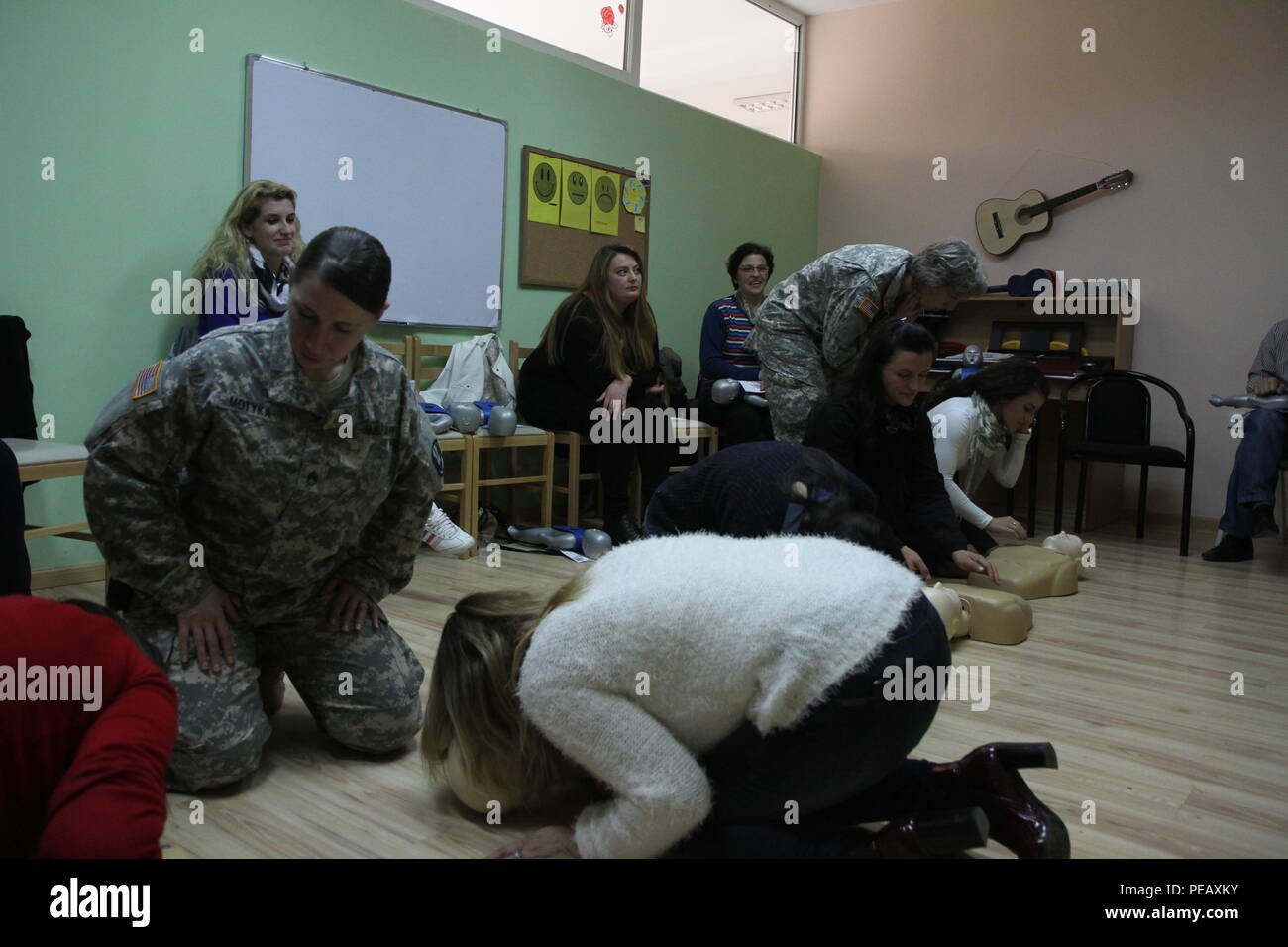 U.S. Army Staff Sgt. Sara Motyka (left) and Capt. Kimberly Keyser, both military medical professionals deployed to Kosovo with Multinational Battle Group-East, observe teachers and caregivers practicing CPR chest compressions during a Nov. 14, 2015, CPR certification class at the PEMA Daycare Center, in Pristina, Kosovo. PEMA provides professional social services for children with disabilities as well as educational classes to the parents, families and caregivers. (U.S. Army photo by Sgt. Gina Russell, Multinational Battle Group-East) Stock Photo