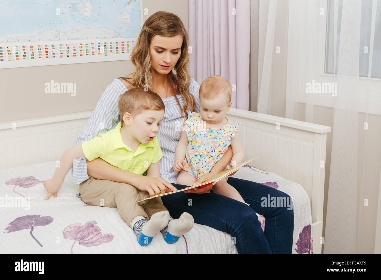 Group portrait of beautiful young white Caucasian mother and little kids sister, brother reading book together indoors at home. Parent with childen si Stock Photo