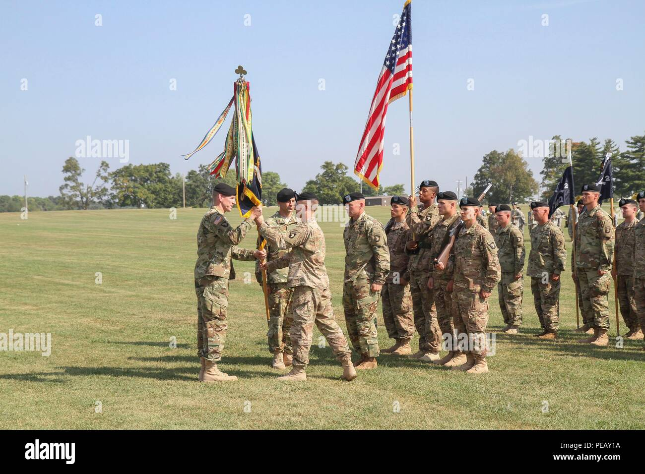 Lt. Col. Christopher Hossfeld, outgoing commander of 2nd Battalion, 327th Infantry Regiment, 1st Brigade Combat Team, 101st Airborne Division, passes the guidon colors to Col. Robert Campbell, 1st Brigade commander, during the battalion's change of command ceremony Sept. 1, 2015, at the Division Parade Field. The passing of the guidon signifies Hossfeld's relinquishing of command and passing the authority on to his successor. (U.S. Army photo by Sgt. Samantha Stoffregen, 1st Brigade Combat Team) - Stock Image