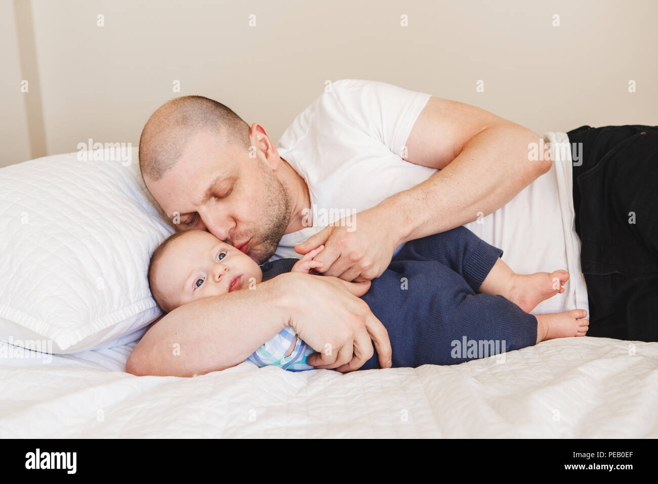 Portrait of middle age Caucasian father in white t-shirt lying in bed with newborn baby son holding his hands fingers, kissing in cheek, parenting chi Stock Photo
