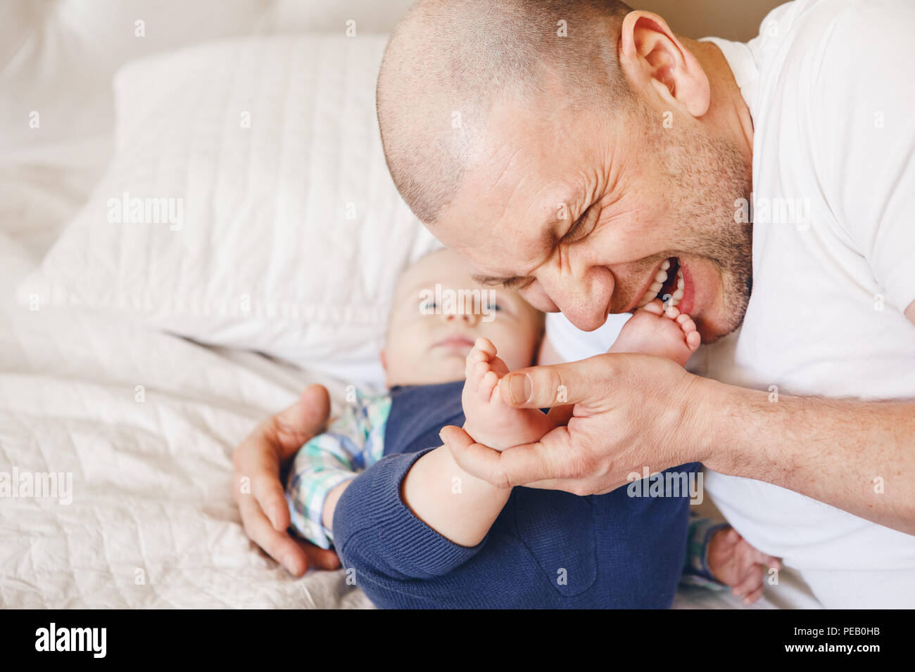 Funny portrait of middle age Caucasian father in white t-shirt lying in bed with newborn baby son kissing biting his feet toes, parenting childhood bo Stock Photo