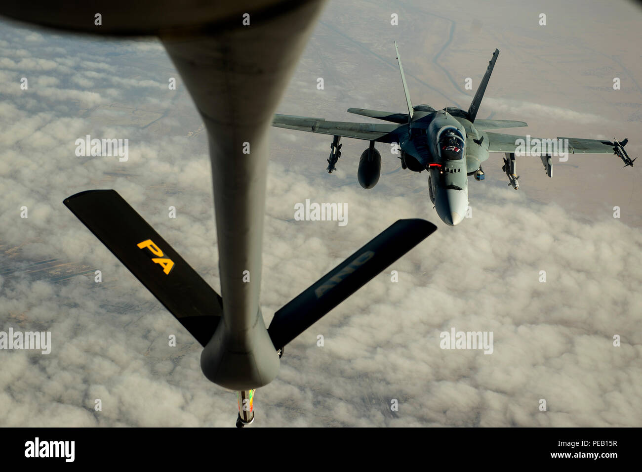 A U.S. Air Force KC-135 Stratotanker from the 340th Expeditionary Air Refueling Squadron prepares to refuel an F-18 from the Royal Canadian Air Force over Southwest Asia in support of Operation Inherent Resolve, Dec. 4, 2015. OIR is the coalition intervention against Daesh. (U.S. Air Force photo by Tech. Sgt. Nathan Lipscomb) Stock Photo