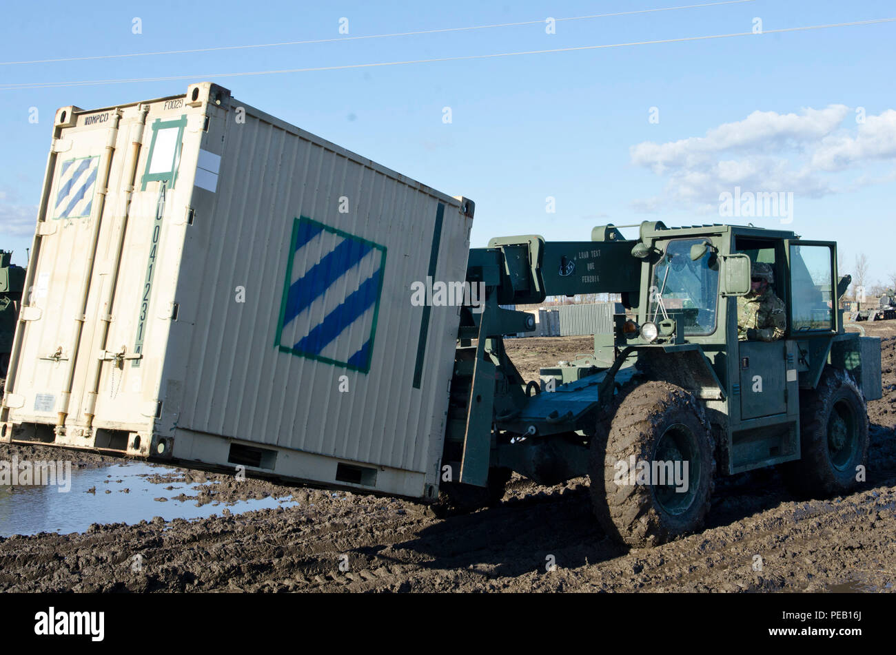 Sgt. Will Davis, a wheeled vehicle mechanic attached to 5th Squadron, 7th Cavalry Regiment, 3rd Infantry Division, Fort Stewart, Ga., originally from Rome, Ga., drives a 10K All Terrain Lifter, Army System Forklift during a transporting operation in Smardan, Romania, Dec. 2, 2015. (U.S. Army Photo by Staff Sgt. Steven M. Colvin/Released) - Stock Image