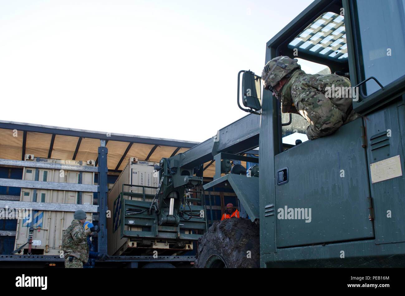 Sgt. Will Davis, a wheeled vehicle mechanic attached to 5th Squadron, 7th Cavalry Regiment, 3rd Infantry Division, Fort Stewart, Ga., originally from Rome, Ga., carefully loads a container onto a trailer as he is guided by Spc. Jose Garrido, a Dealer Troop armorer of 5/7 Cav., originally from Puerto Rico, during a transporting operation in Smardan, Romania, Dec. 2, 2015. (U.S. Army Photo by Staff Sgt. Steven M. Colvin/Released) - Stock Image