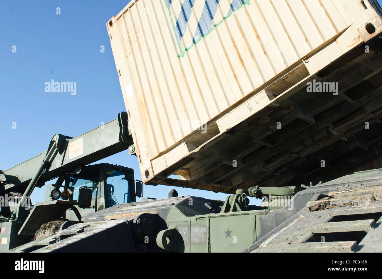 Sgt. Will Davis, a wheeled vehicle mechanic attached to 5th Squadron, 7th Cavalry Regiment, 3rd Infantry Division, Fort Stewart, Ga., originally from Rome, Ga., carefully places a container onto the trailer of an M1070 Heavy Equipment Transporter System during a transporting operation in Smardan, Romania, Dec. 2, 2015. (U.S. Army Photo by Staff Sgt. Steven M. Colvin/Released) - Stock Image