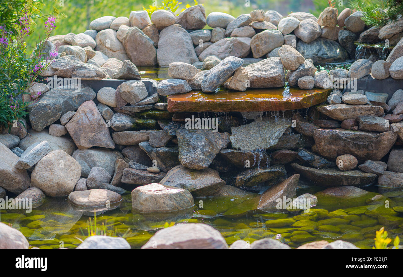 Small Waterfall In A Garden Made From Rocks