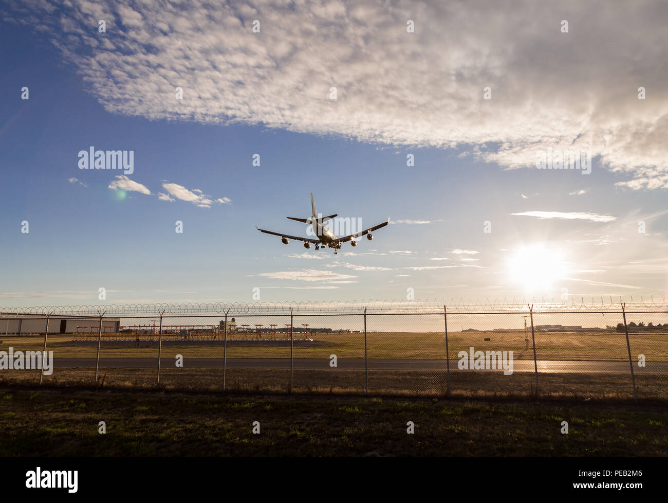 An aircraft on final at YVR with the sunset in the background. Stock Photo