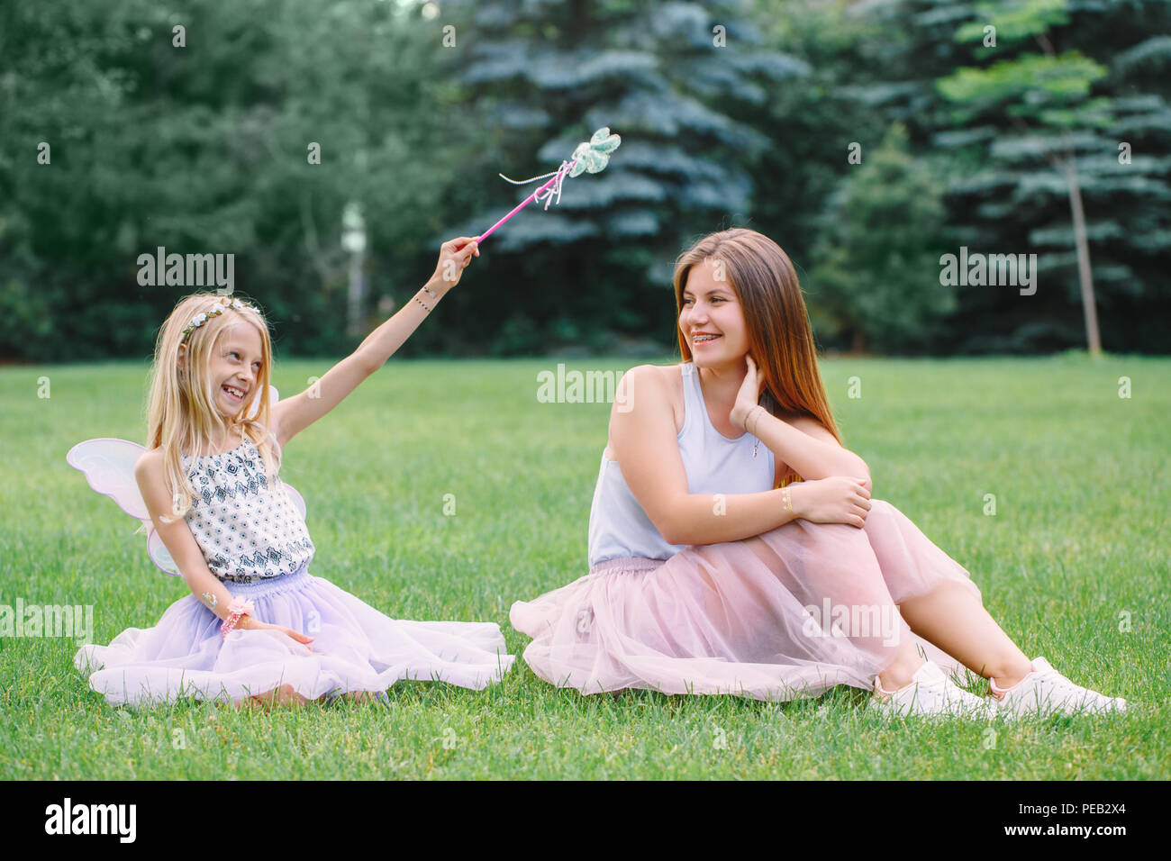 Portrait of two smiling funny Caucasian girls sisters wearing pink tutu tulle skirts in park forest meadow at sunset. Friends having fun together. Gir - Stock Image