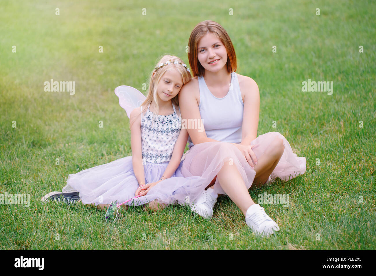 7713c98c2c Portrait of two smiling funny Caucasian girls sisters wearing pink tutu  tulle skirts in park forest