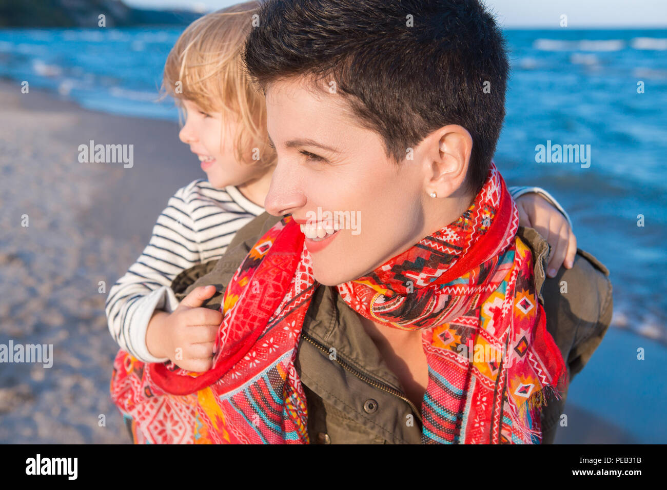 Group portrait of smiling white Caucasian mother and daughter baby girl, piggy back riding, playing running on ocean sea beach at sunset outdoors, hap - Stock Image