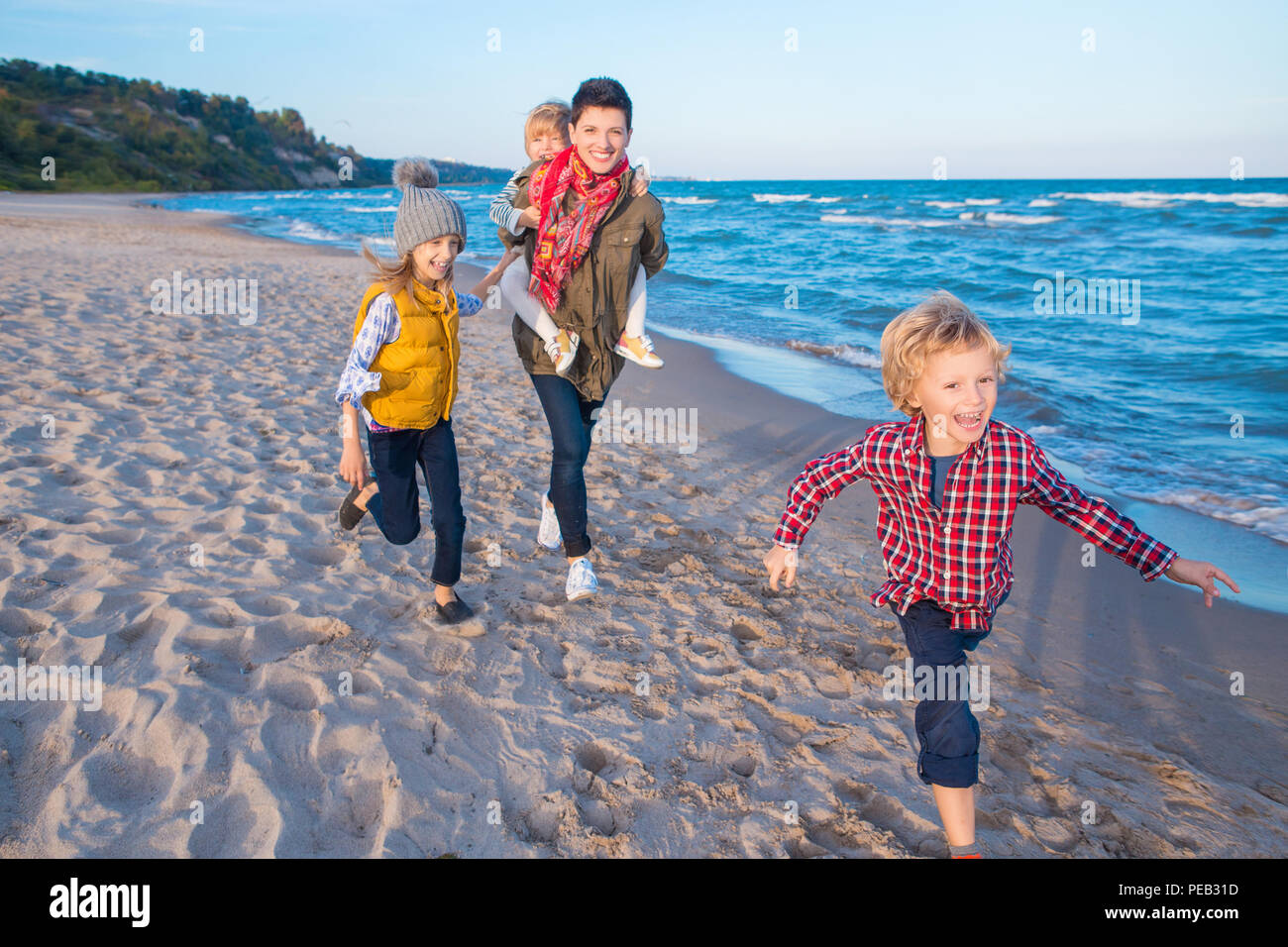 Group portrait of three funny smiling laughing white Caucasian children kids with mother running on ocean sea beach at sunset outdoors, happy lifestyl - Stock Image