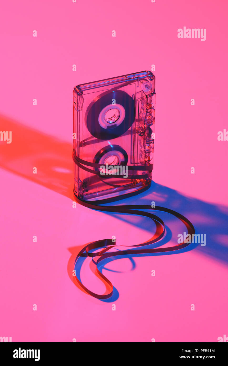 close up view of retro audio cassette and tape on pink backdrop - Stock Image
