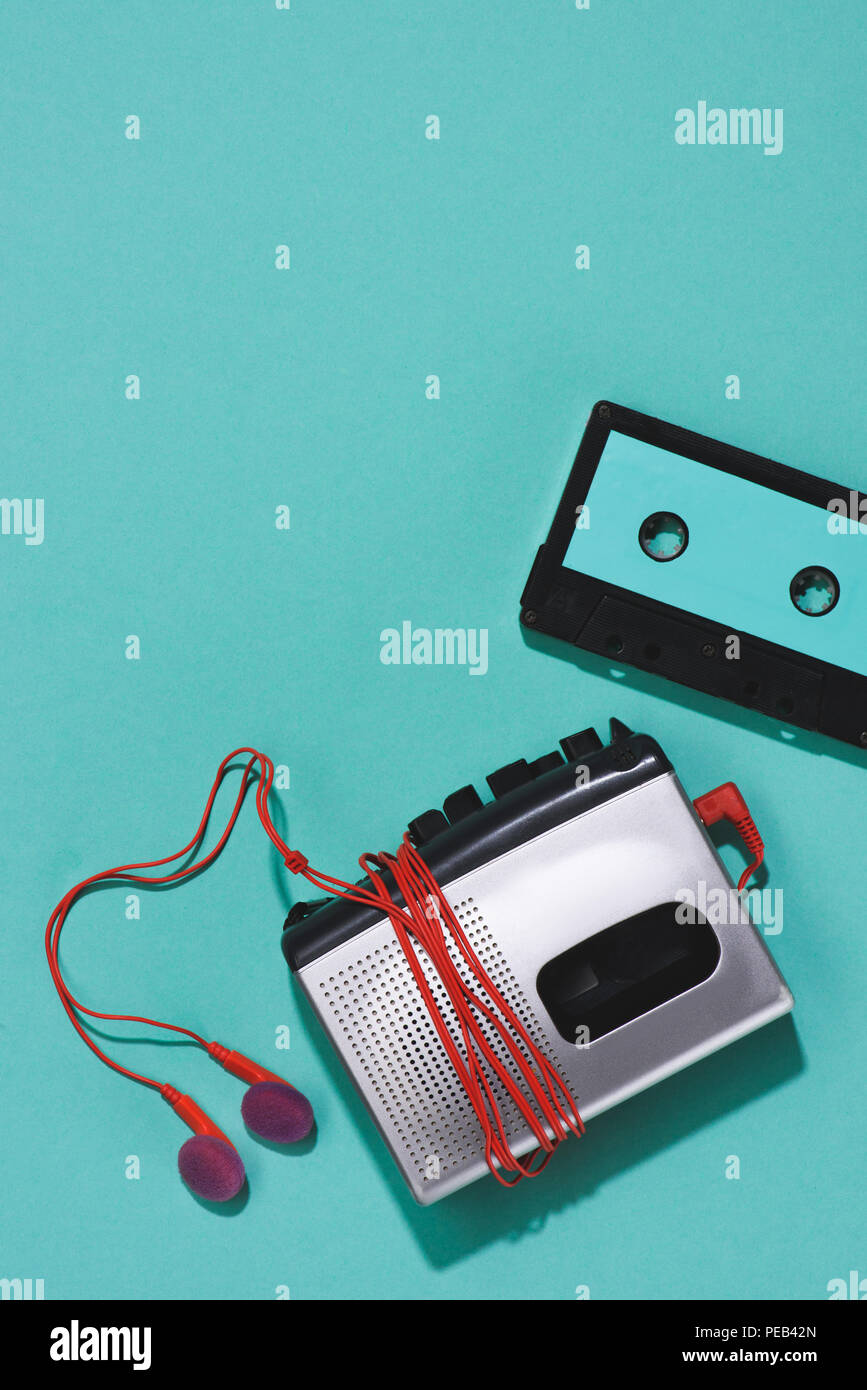 flat lay with retro audio cassette, cassette player and earphones isolated on blue - Stock Image