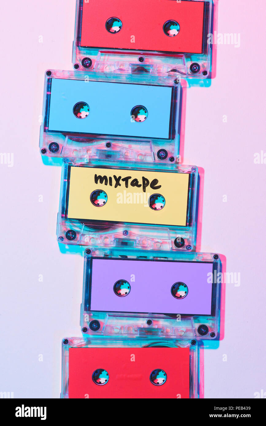 top view of arranged colorful audio cassettes with mixtape lettering on purple background - Stock Image