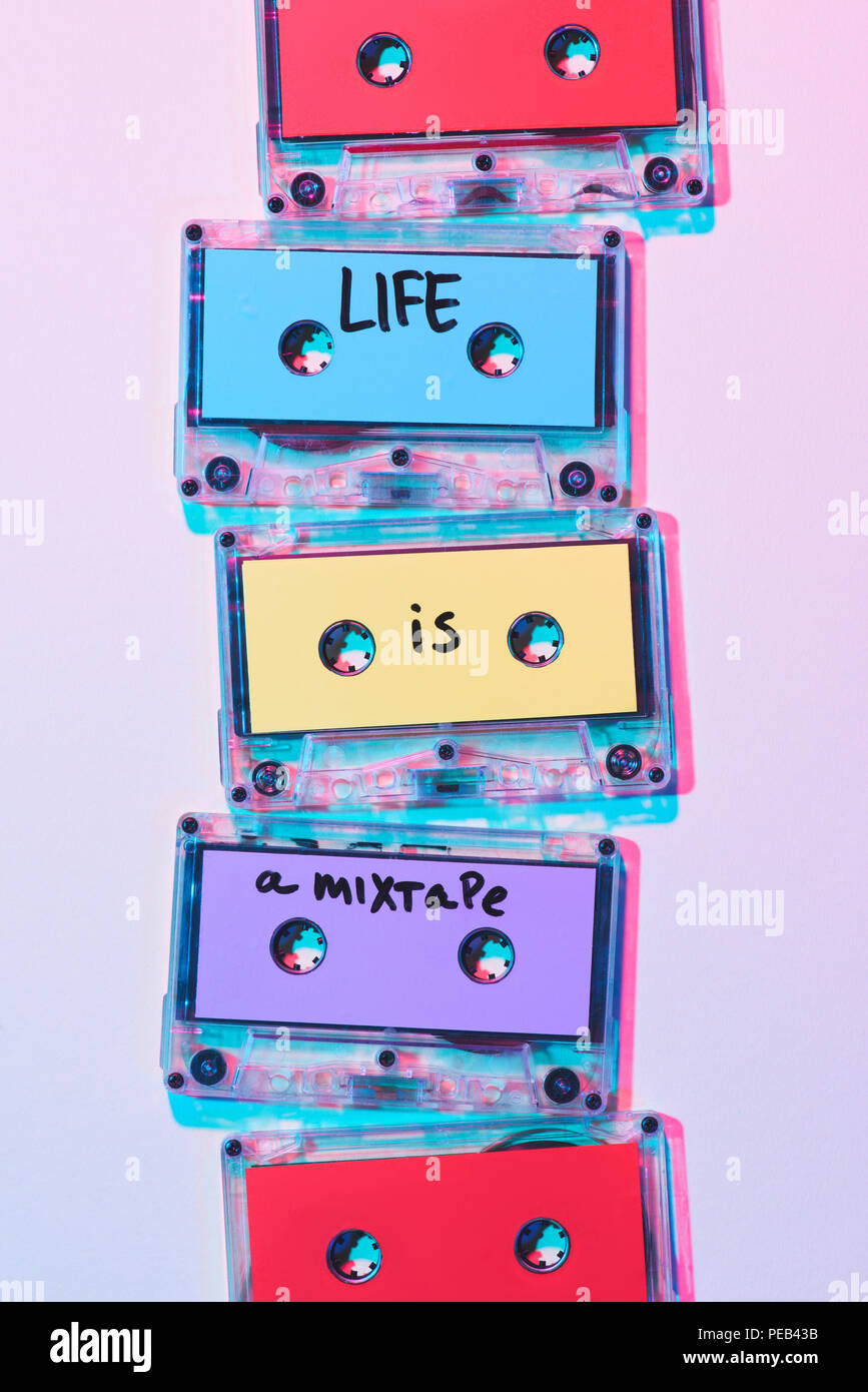 top view of arranged colorful audio cassettes with life is a mixtape inscription on purple background - Stock Image