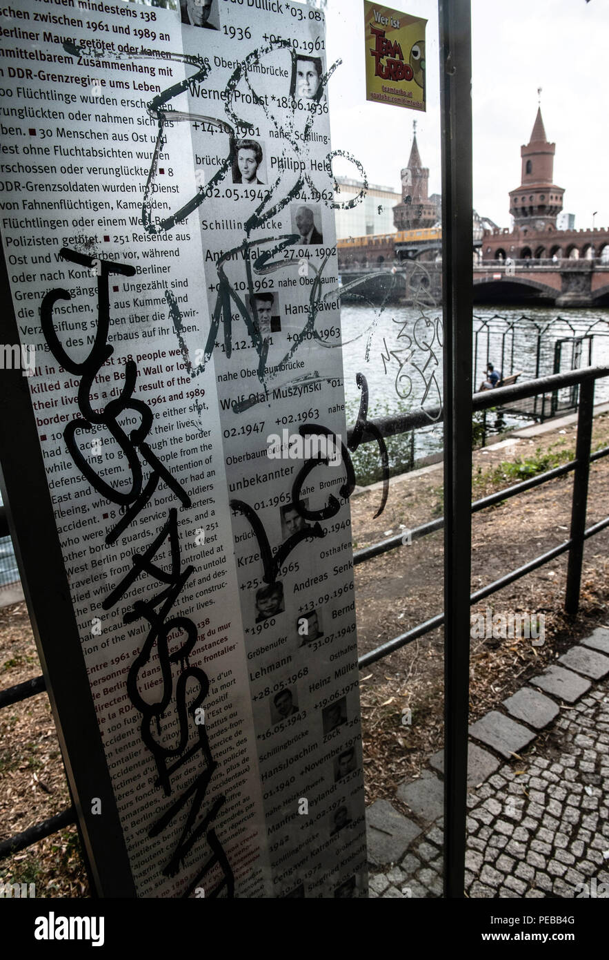 Germany, Berlin. 14th Aug, 2018. The memorial plaques for the dead on the banks of the Spree near the Oberbaum Bridge have been smeared. Unknown sprayers have smeared graffiti on the two plates for the Wall Death and stolen a funeral wreath. The police are investigating for property damage. Credit: Paul Zinken/dpa/Alamy Live News - Stock Image