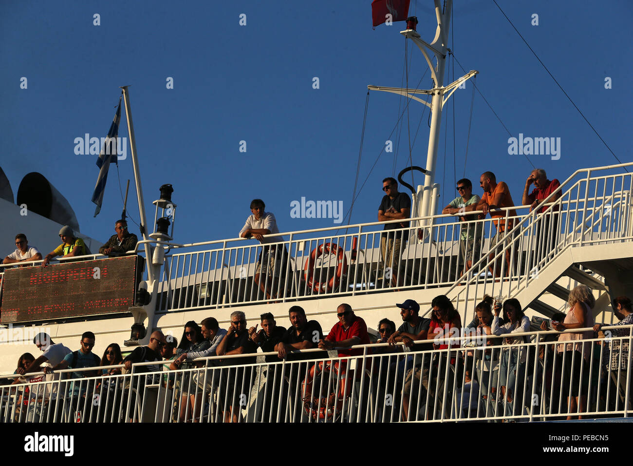 Piraeus, Greece. 14th Aug, 2018. Passengers wait on deck of a ferry ready to depart from Piraeus, ahead of the traditional mid-August exodus around Aug. 15, a national holiday, in Piraeus, Greece, on Aug. 14, 2018. Credit: Marios Lolos/Xinhua/Alamy Live News - Stock Image