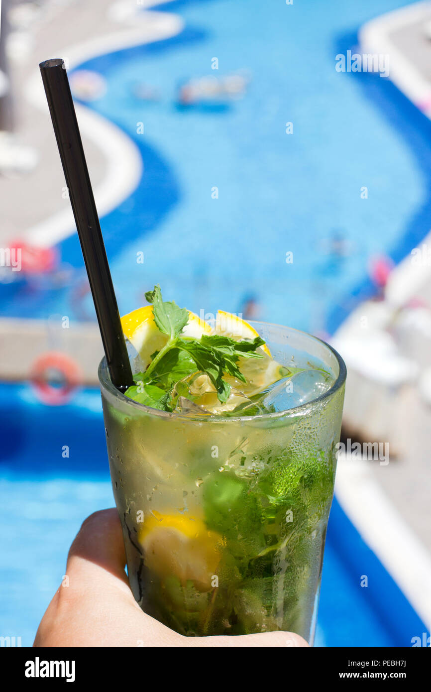 Hand holding Mojito cocktail on the background of a pool - Stock Image