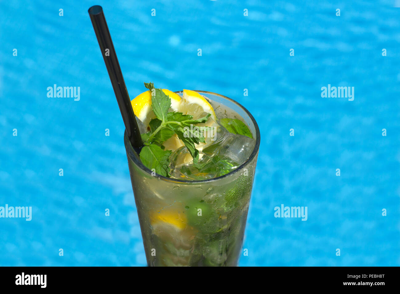 Mojito cocktail in glass on the background of a pool - Stock Image