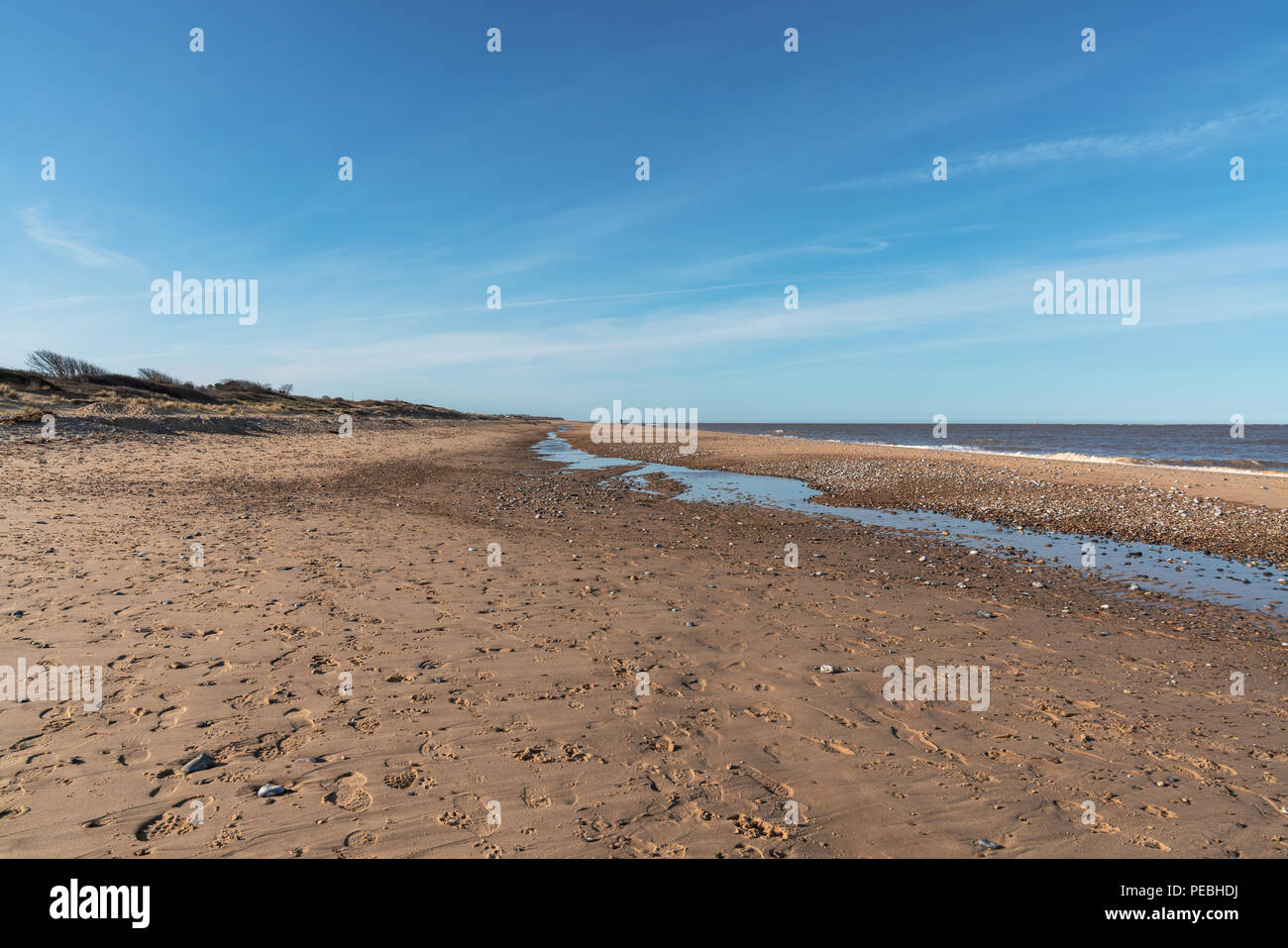 North sea coast in Caister-on-Sea, Norfolk, England, UK - the almost empty beach with someone walking in the backgorund Stock Photo