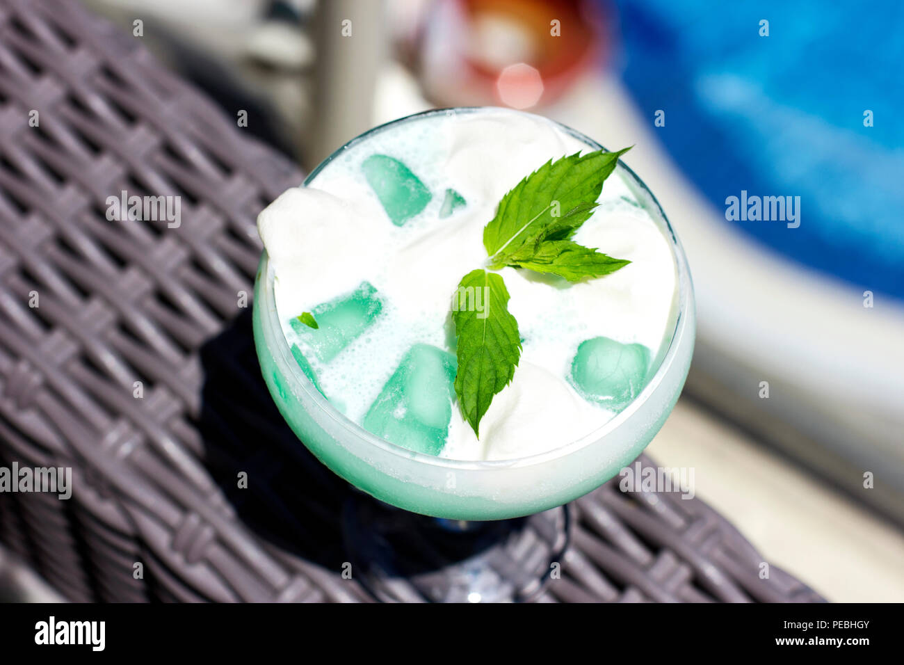 Blue cocktail in a pot-bellied glass with ice cream and green mint leaves - Stock Image
