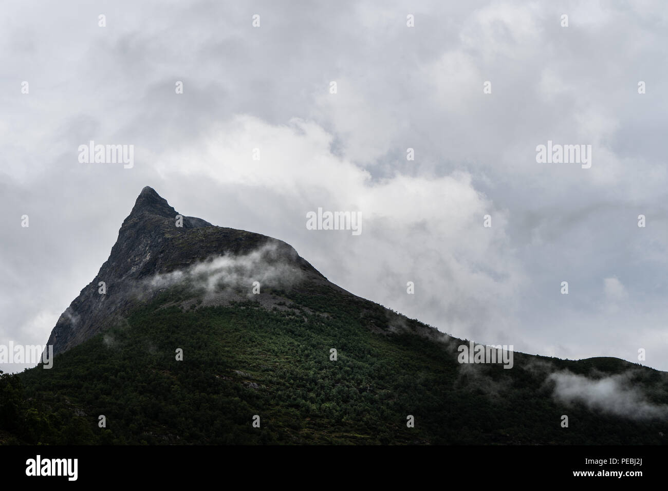 Pointy mountain and cloudy weather - Stock Image