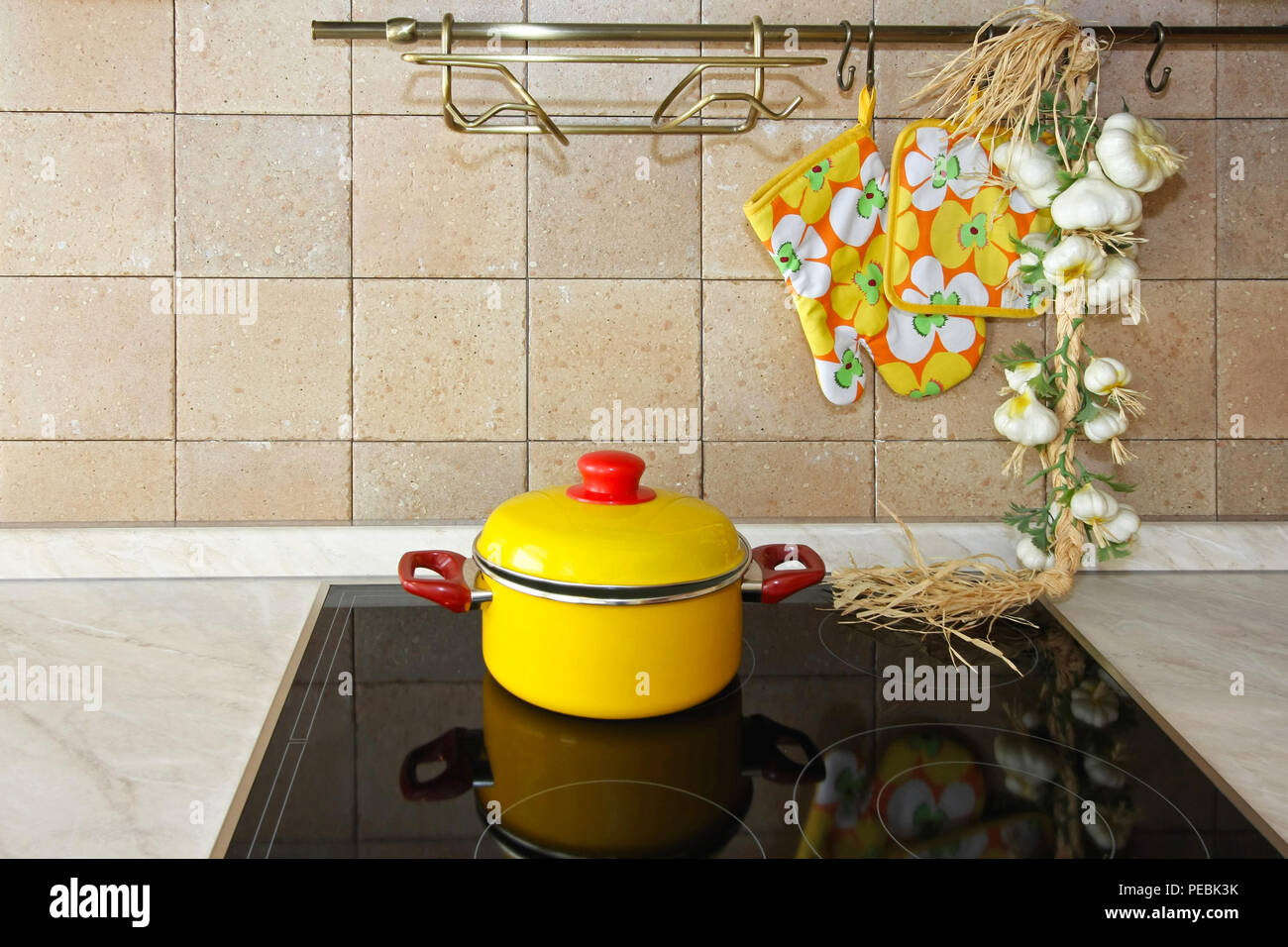 Yellow pot at ceramic stove in kitchen - Stock Image