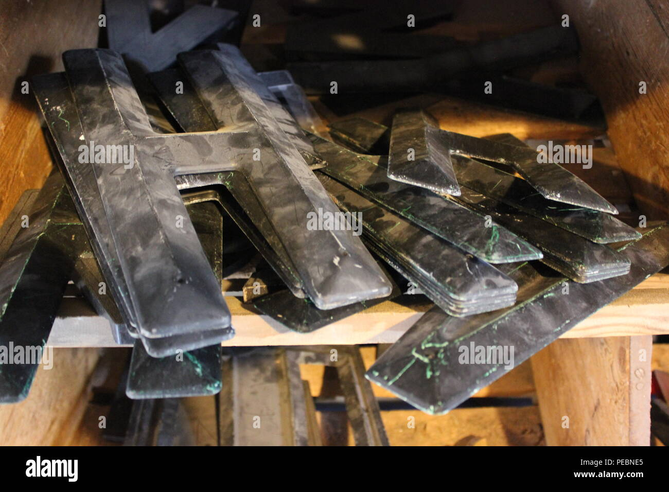 Black plastic dusty capital letters in storage on a shelf at Architectural Artifacts in Chicago, Illinois. - Stock Image