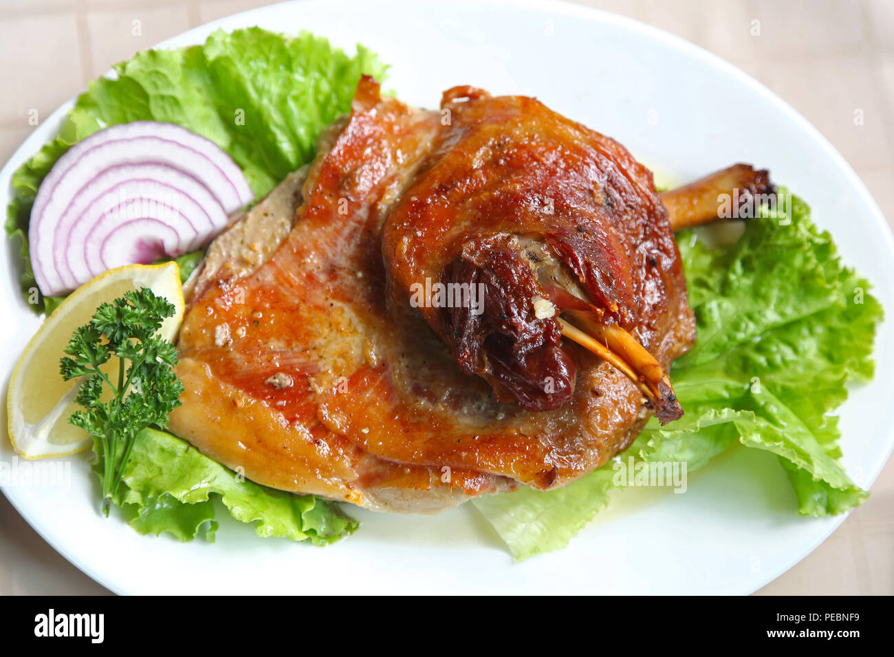 Roasted lamb shank served at dish with salad - Stock Image
