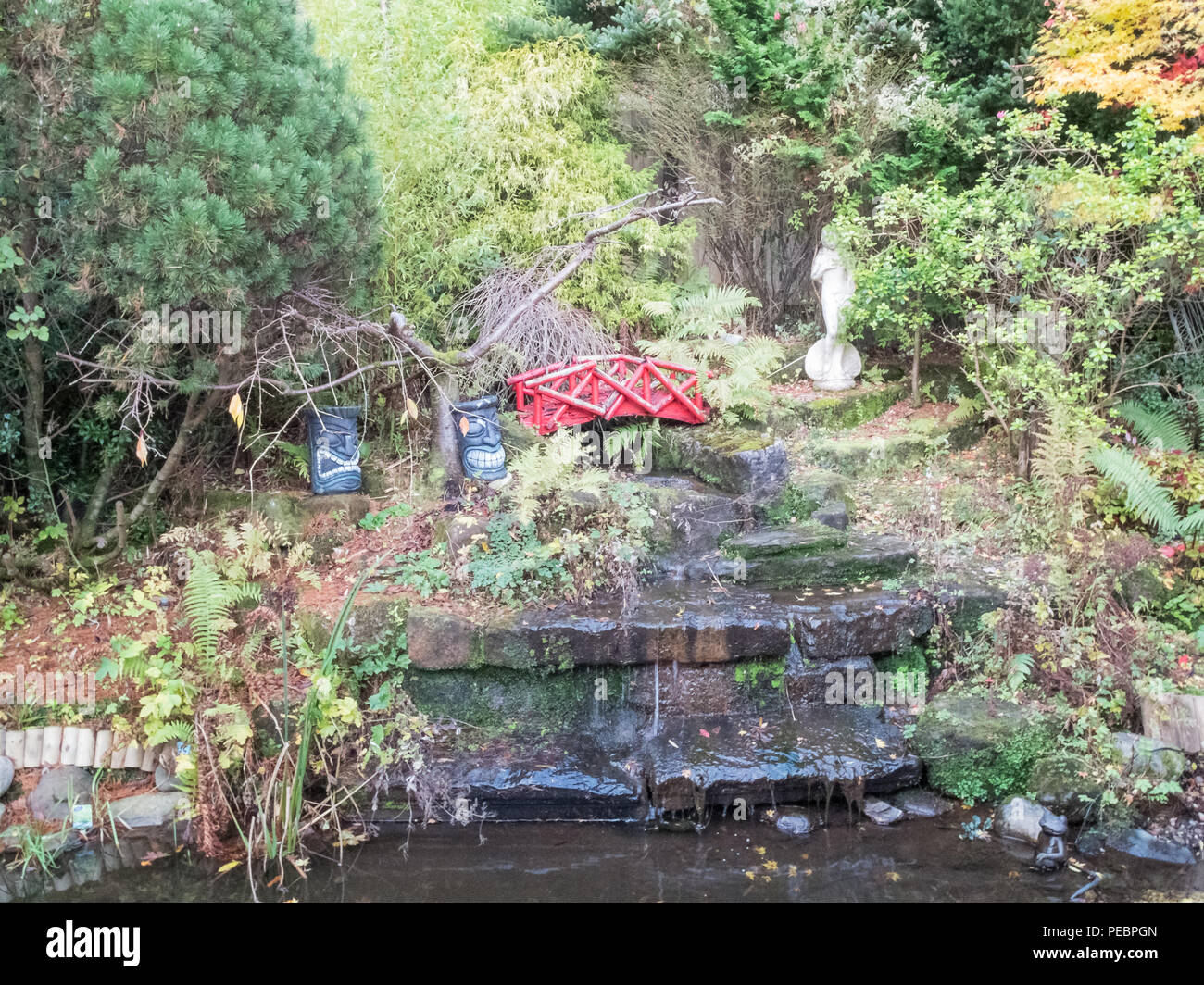 A minature garden waterfall feature with ornaments and running water. - Stock Image