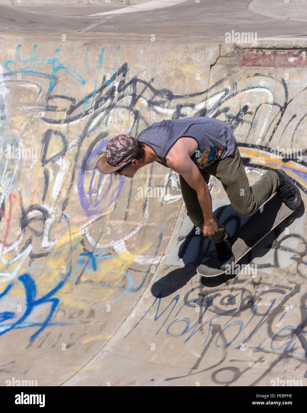 Young Man Skateboarding at the Riverside River Yard Skateboard Bowl, Great Fall, Montana, USA - Stock Image