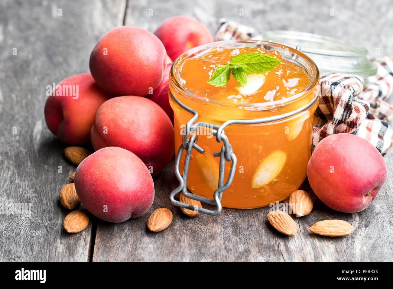 Red apricot  jam with almonds in a clear glass jar on wooden table - Stock Image