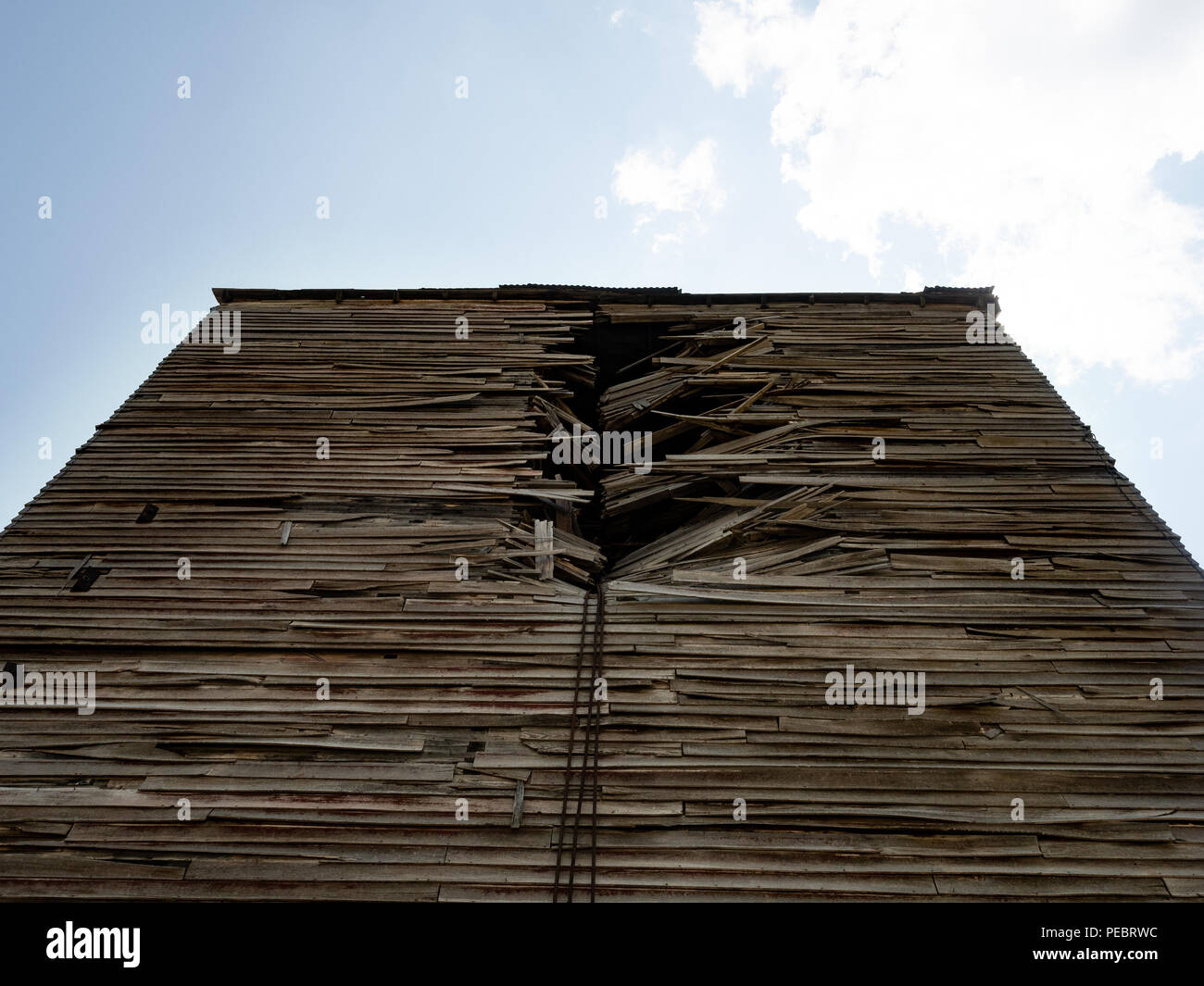 Close up of an old, damaged clapboard wood building photographed from below. - Stock Image