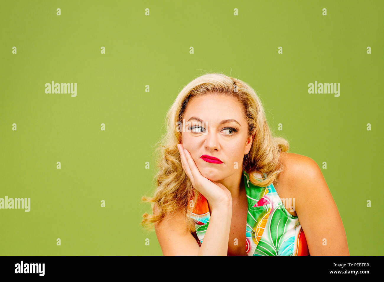 Portrait of an envious woman in bad mood looking right, isolated on green studio background - Stock Image