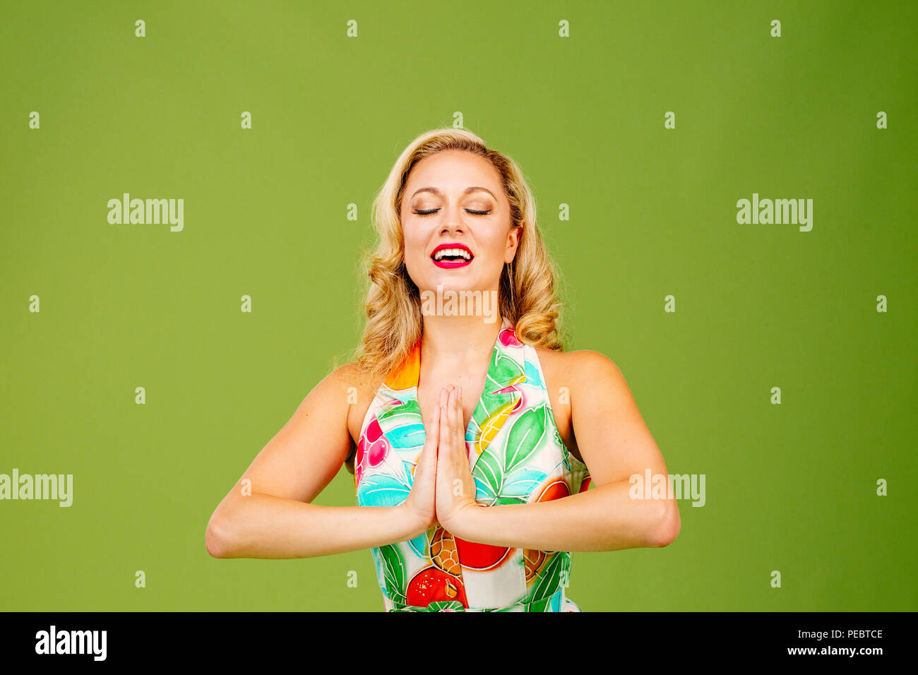 Beautiful woman with hands together in prayer and mouth open, isolated on green studio background - Stock Image