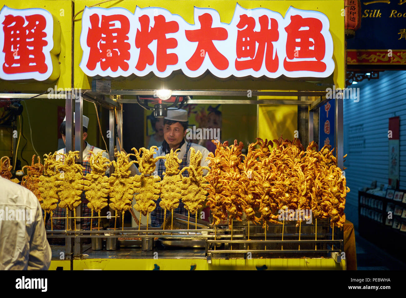 Fried and Grilled Squid on a Stick Sold by a Street Vendor, Muslim Quarter, Xi'an, Shaanxi, China - Stock Image