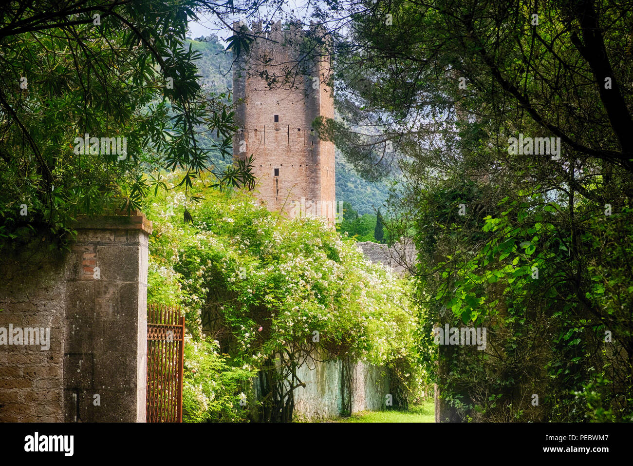 Garden Entrance with a Medieval Tower, Garden of Ninfa, Cisterna di Latina , Italy - Stock Image
