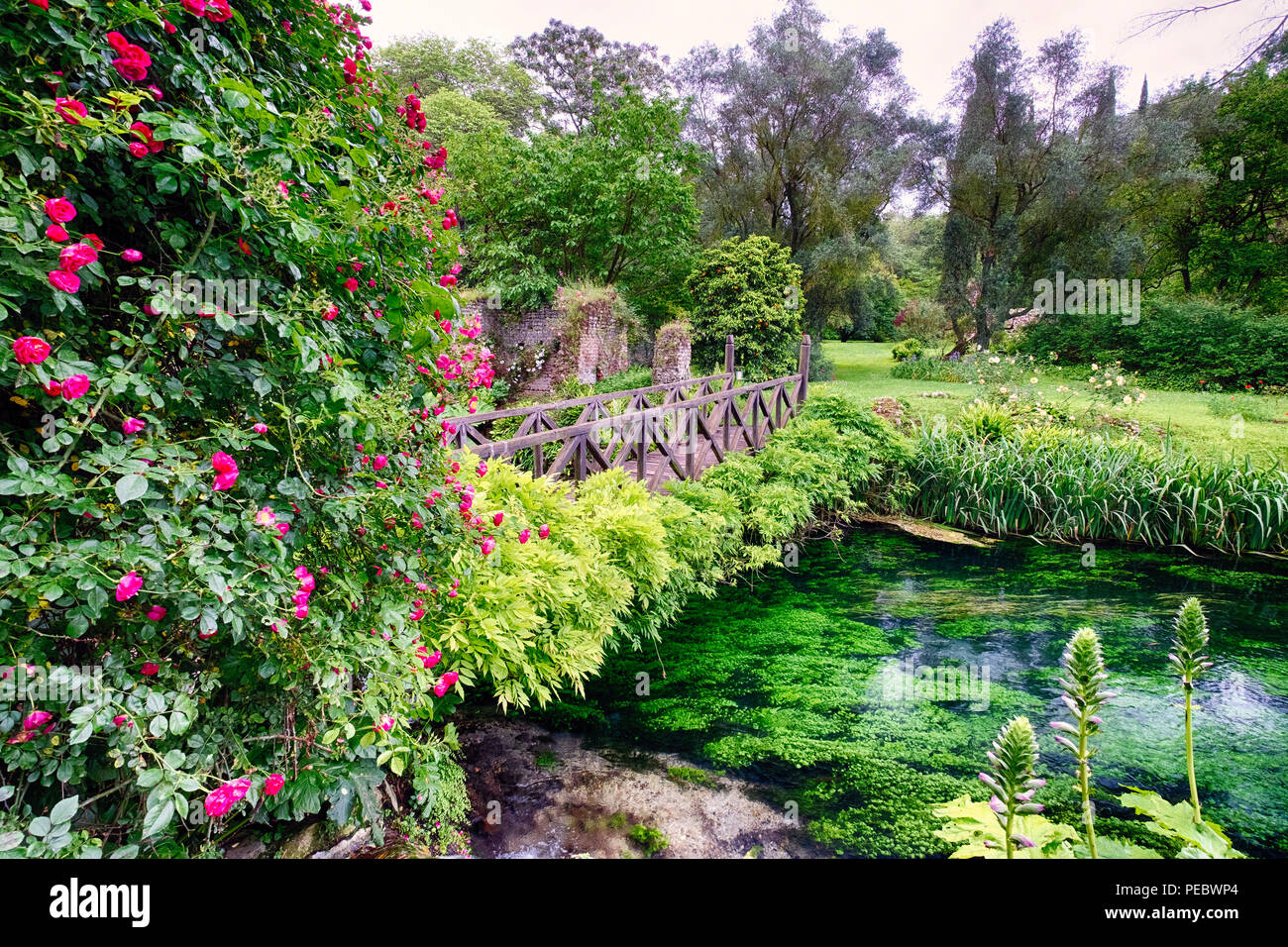 Small Footbridge Over a Creek  in a the Ninfa Garden, Cisterna di Latina, Italy - Stock Image