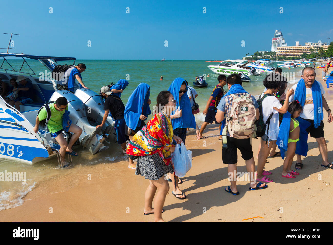 Chinese tourists returning from boat trip, Pattaya, Thailand - Stock Image