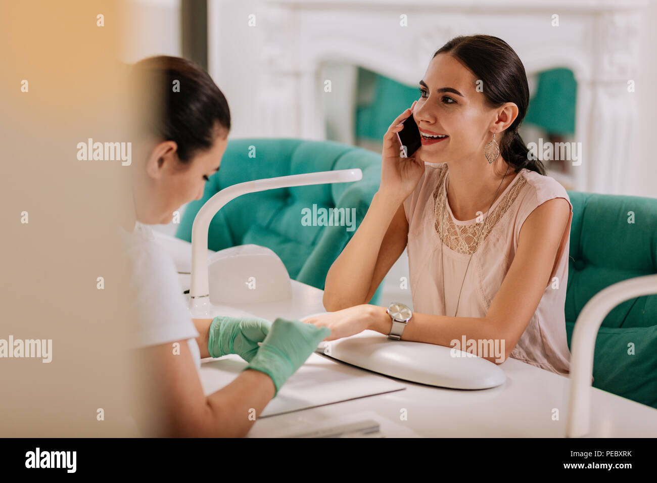 Busy businesswoman speaking on the telephone while having manicure - Stock Image