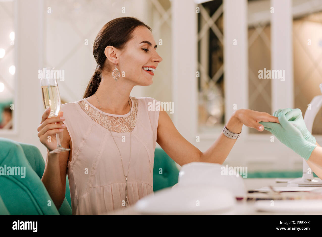 Successful businesswoman enjoying classy service in famous nail bar - Stock Image