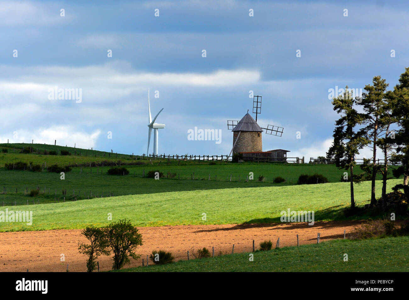 Windmill and wind turbine together in the middle of cultivated fields in summer, Allier windfarm, Haute Loire department, Auvergne, France, Europe - Stock Image