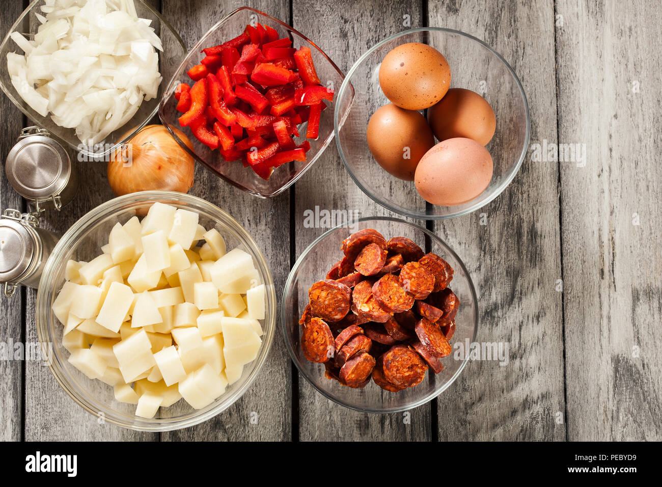 Tortilla de patatas. Ingredients for preparing spanish omelette with sausage chorizo, potatoes, paprika and egg. Spanish cuisine - Stock Image