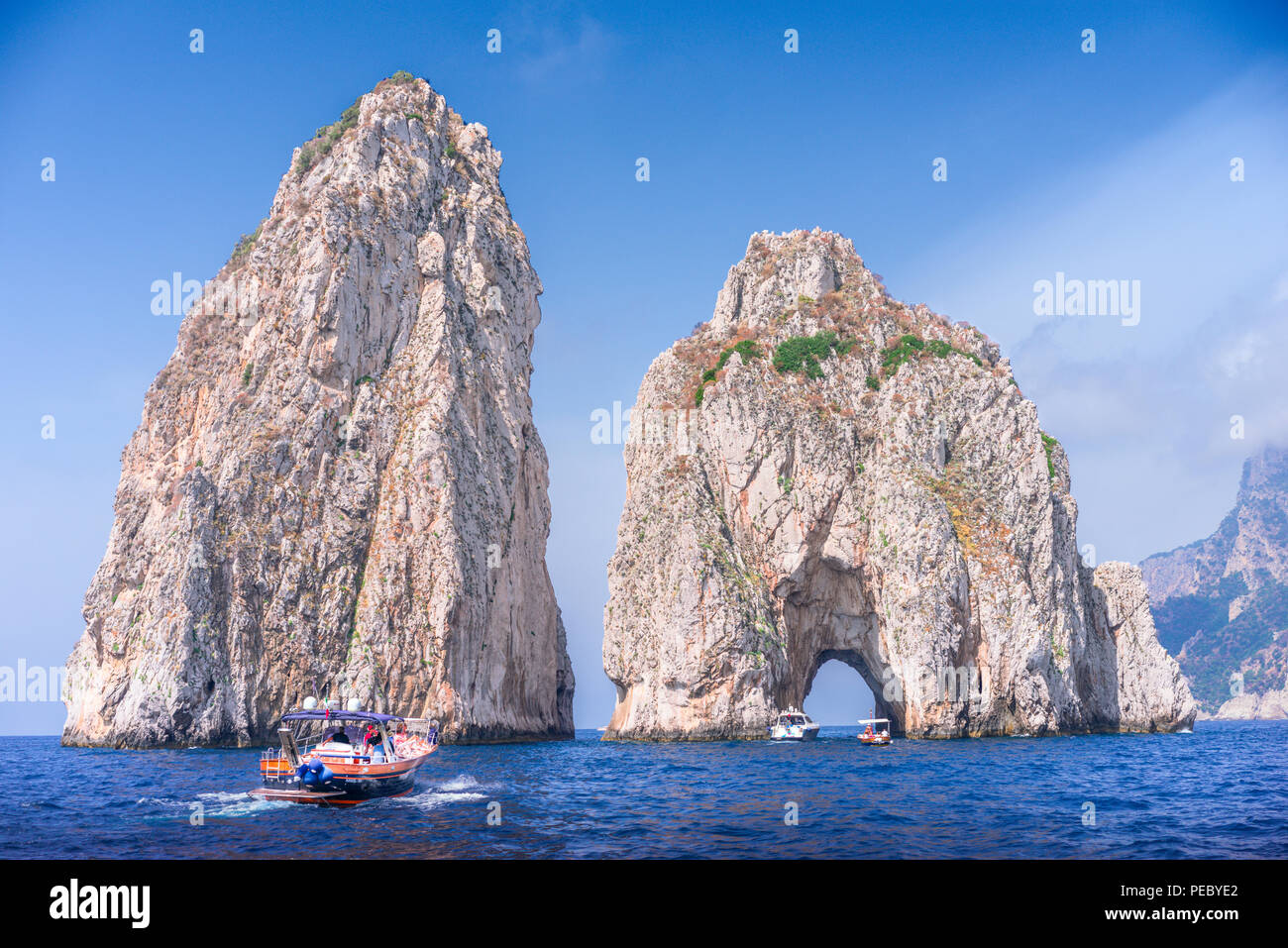 Approaching the Faraglioni by boat these are stacks formed from rocks on the southern side of Capri, one distinguishing feature is the archway - Stock Image