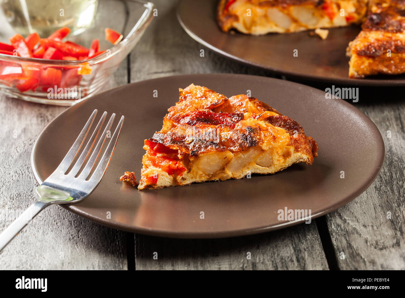 Tortilla de patatas. Spanish omelette with sausage chorizo, potatoes, paprika and egg, accompanied by olive oil. Spanish cuisine - Stock Image